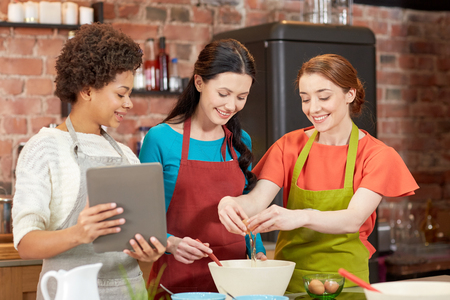 cooking class, friendship, food, technology and people concept - happy women with tablet pc in kitchen