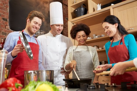 classes: cooking class, culinary, food and people concept - happy group of friends and male chef cook cooking in kitchen Stock Photo