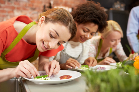 cooking class, friendship, food and people concept - happy women cooking and decorating plates with dishes in kitchen