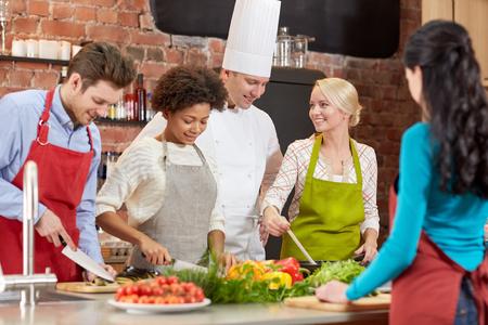Kochkurs, kulinarisch, Essen und die Leute Konzept - glücklich Gruppe von Freunden und männliche Chefkoch in der Küche kochen Standard-Bild