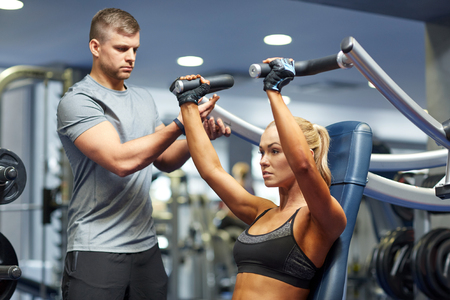 personal training: sport, fitness, bodybuilding, teamwork and people concept - young woman and personal trainer flexing muscles on gym machine Stock Photo