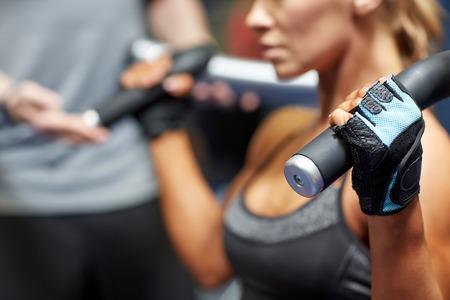 pesas: deporte, fitness, musculación, trabajo en equipo y la gente concepto - mujer joven y entrenador personal flexionar los músculos en la máquina de gimnasio