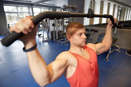 muscle training: Sport, Fitness, Bodybuilding, Lifestyle und Menschen Konzept - ein Mann trainieren und Muskeln auf Kabel-Maschine in der Gymnastik biegt Lizenzfreie Bilder