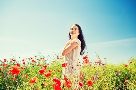 vacation summer: happiness, nature, summer, vacation and people concept - smiling young woman on poppy field