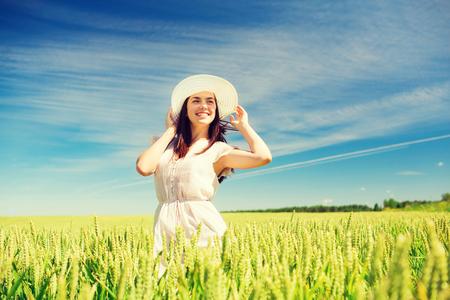 幸福、自然、夏、休暇および人々 のコンセプト - 穀物のフィールドに身に着けている麦わら帽子を若い女性を笑顔