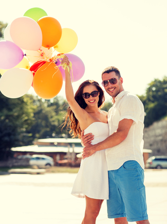 latin family: love, wedding, summer, dating and people concept - smiling couple wearing sunglasses with balloons hugging in park
