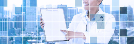 grid paper: health care, people and medical concept - happy african female doctor pointing finger to blank paper on clipboard over city and blue grid background Stock Photo