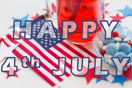food state: happy american independence day, celebration, patriotism and holidays concept - close up of juice glass, flag and candies at 4th july party