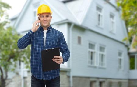 portapapeles: reparación, construcción, construcción, bienes raíces y mantenimiento concepto - la sonrisa del hombre o constructor en casco con el portapapeles llamando en el teléfono inteligente más que viven fondo de la casa