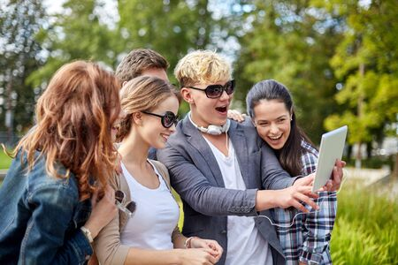summer holidays: summer, technology, education and teenage concept - group of happy students or teenagers with tablet pc computer taking selfie