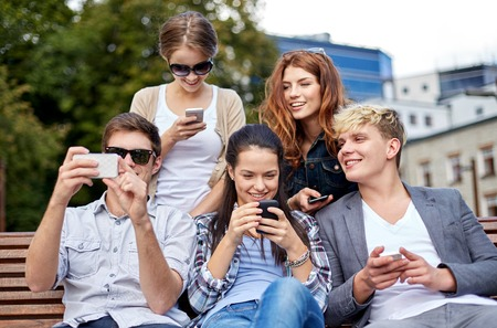 mobile phones: summer, technology, education and teenage concept - group of happy students or teenagers with smarphones taking selfie and texting messages at campus