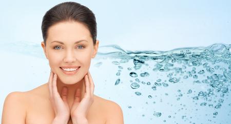 oxygen: belleza, gente, hidratación y el concepto de salud - mujer joven con los hombros descubiertos que toca su cara más de las salpicaduras de agua sobre fondo azul sonriendo