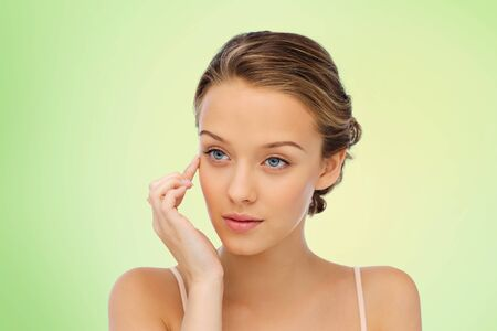 natural beauty: beauty, people, cosmetics, skincare and health concept - young woman applying cream to her face over green natural background