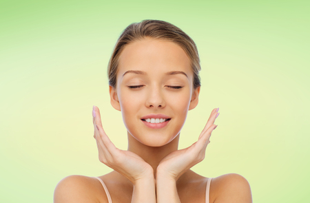 natural face: beauty, people, skincare and health concept - smiling young woman face and hands over green natural background Stock Photo