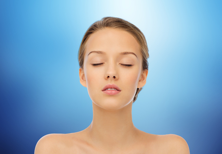 beauty, people and health concept - young woman face with closed eyes and shoulders over marine blue background