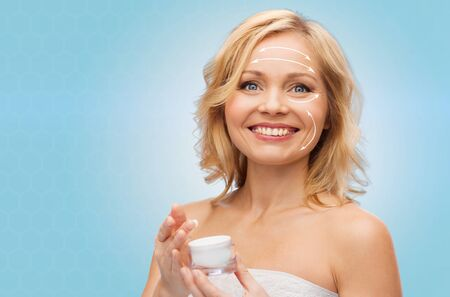 antiaging: beauty, people, skincare, anti-aging and cosmetics concept - happy woman with cream jar over blue background