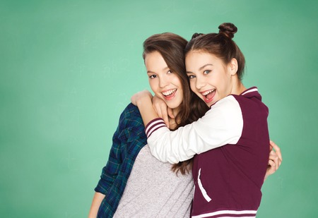 teenagers: people, friends, teens and education concept - happy smiling pretty teenage girls hugging over green school chalk board background