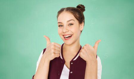 concept de personnes, l'éducation, le geste et les adolescents - heureuse souriante jolie adolescente fille montrant les pouces vers le haut sur fond de tableau vert école craie