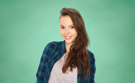 cute teen: people, education and teens concept - happy smiling pretty teenage student girl over green school chalk board background