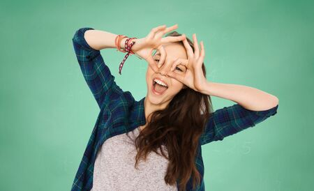 people, education and teens concept - happy smiling pretty teenage girl making face and having fun over green school chalk board background