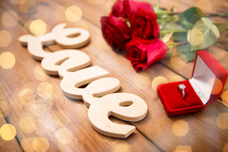 attentions: proposal, romance, valentines day and holidays concept - close up of gift box with diamond engagement ring, red roses and word love on wood Stock Photo