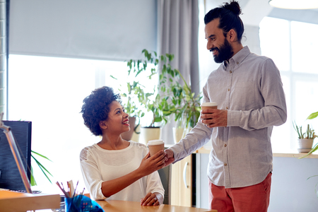 african business man: business, startup, people and drinks concept - happy latin man bringing coffee to african woman in office