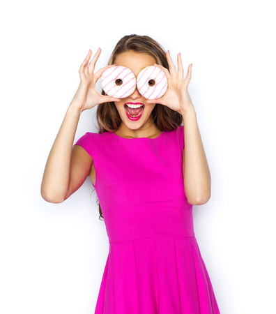 cheerful: people, holidays, junk food and fast food concept - happy young woman or teen girl in pink dress having fun and looking through donuts Stock Photo
