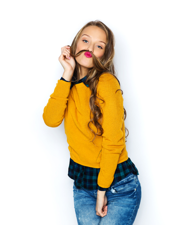 mustache: people, style and fashion concept - happy young woman or teen girl in casual clothes having fun making mustache of her hair strand