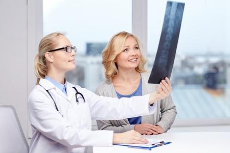 la medicina, l'età, l'assistenza sanitaria e la gente concetto - paziente donna felice e medico con colonna vertebrale x-ray incontro scansione in ufficio medico