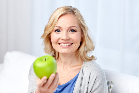 aged: healthy eating, organic food, fruits, diet and people concept - happy middle aged woman with green apple at home