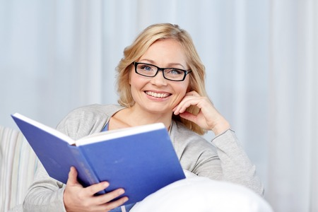 living wisdom: leisure, literature and people concept - smiling middle aged woman reading book and sitting on couch at home