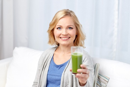 green vegetable: healthy eating, vegetarian food, dieting, detox and people concept - smiling middle aged woman drinking green fresh vegetable juice or smoothie from glass at home