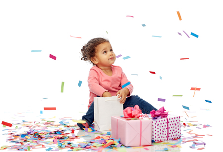 bebe sentado: childhood, birthday, party, holidays and people concept - happy little african american baby girl with gift boxes and confetti playing with shopping bag sitting on floor Foto de archivo