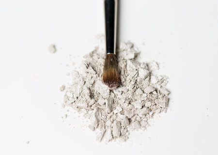 up view: cosmetics, makeup and beauty concept - close up of makeup brush and eyeshadow