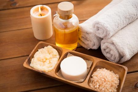 belleza, spa, cuidado del cuerpo, cosméticos naturales y el concepto de bienestar - cerca de jabón con velas y toallas de baño en la mesa de madera Foto de archivo
