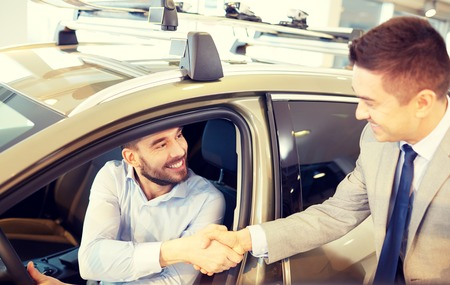 deal in: auto business, car sale, consumerism, gesture and people concept - happy man with car dealer making deal and shaking hands in auto show or salon