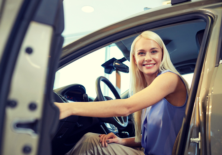 drive car: auto business, car sale, consumerism , transportation and people concept - happy woman sitting in or driving car