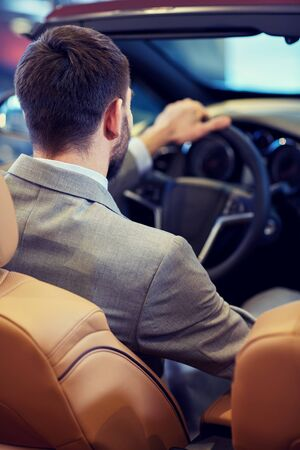 business lifestyle: auto business, car sale, lifestyle and people concept - close up of man sitting in cabriolet car at auto show or salon