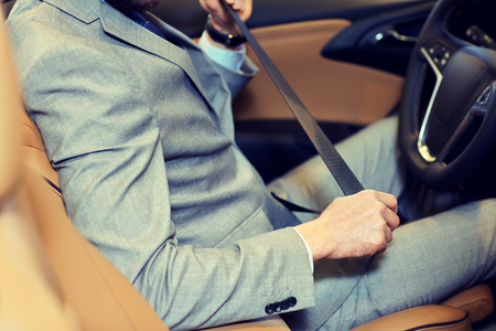 fastening: safety, driving and people concept - close up of man in elegant business suit fastening seat safety belt in car