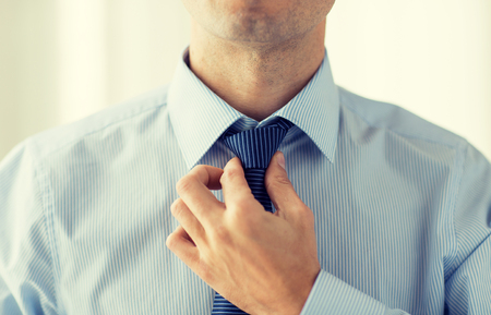 people, business, fashion and clothing concept - close up of man in shirt dressing up and adjusting tie on neck at home Stock Photo