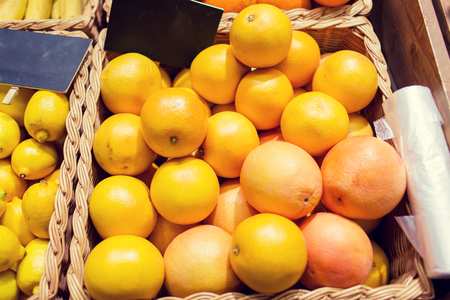 nameplate: sale, shopping, vitamin c and healthy food concept - ripe grapefruits in basket with nameplate at grocery market