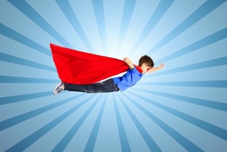 air movement: happiness, freedom, childhood, movement and people concept - boy in red superhero cape and mask flying in air over blue burst rays background Stock Photo