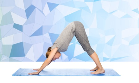dog pose: fitness, sport, people and healthy lifestyle concept - woman making yoga in downward facing dog pose on mat over low poly background