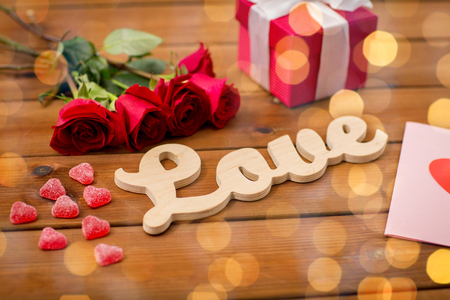 uprzejmości: romance, valentines day and holidays concept - close up of word love, gift box, red roses and greeting card with heart-shaped candies and golden lights on wood