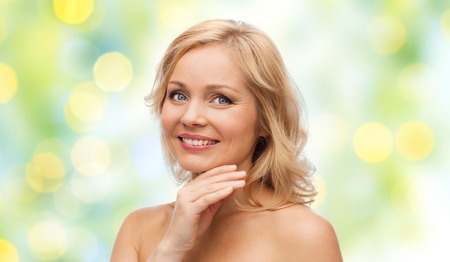 smile face: beauty, people and skincare concept - smiling middle aged woman with bare shoulders touching face over green holidays lights background Stock Photo