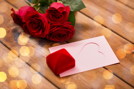 attentions: love, romance, valentines day and holidays concept - close up of gift box, red roses and greeting card with heart and golden lights on wood