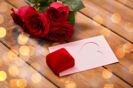 uprzejmości: miłość, romans, Walentynki i święta pojęcie - zamknąć pudełko, czerwone róże i kartkę z życzeniami z serca i złote światełka na drewnie