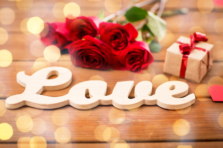 uprzejmości: love, romance, valentines day and holidays concept - close up of gift box, red roses and hearts on wood over golden lights