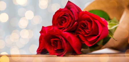 attentions: love, date, flowers, valentines day and holidays concept - close up of red roses bunch wrapped into brown paper on wooden table over golden lights