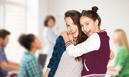 school, education, people, teens and friendship concept - happy smiling pretty teenage student girls hugging over classroom background with teacher and classmates Stock Photo